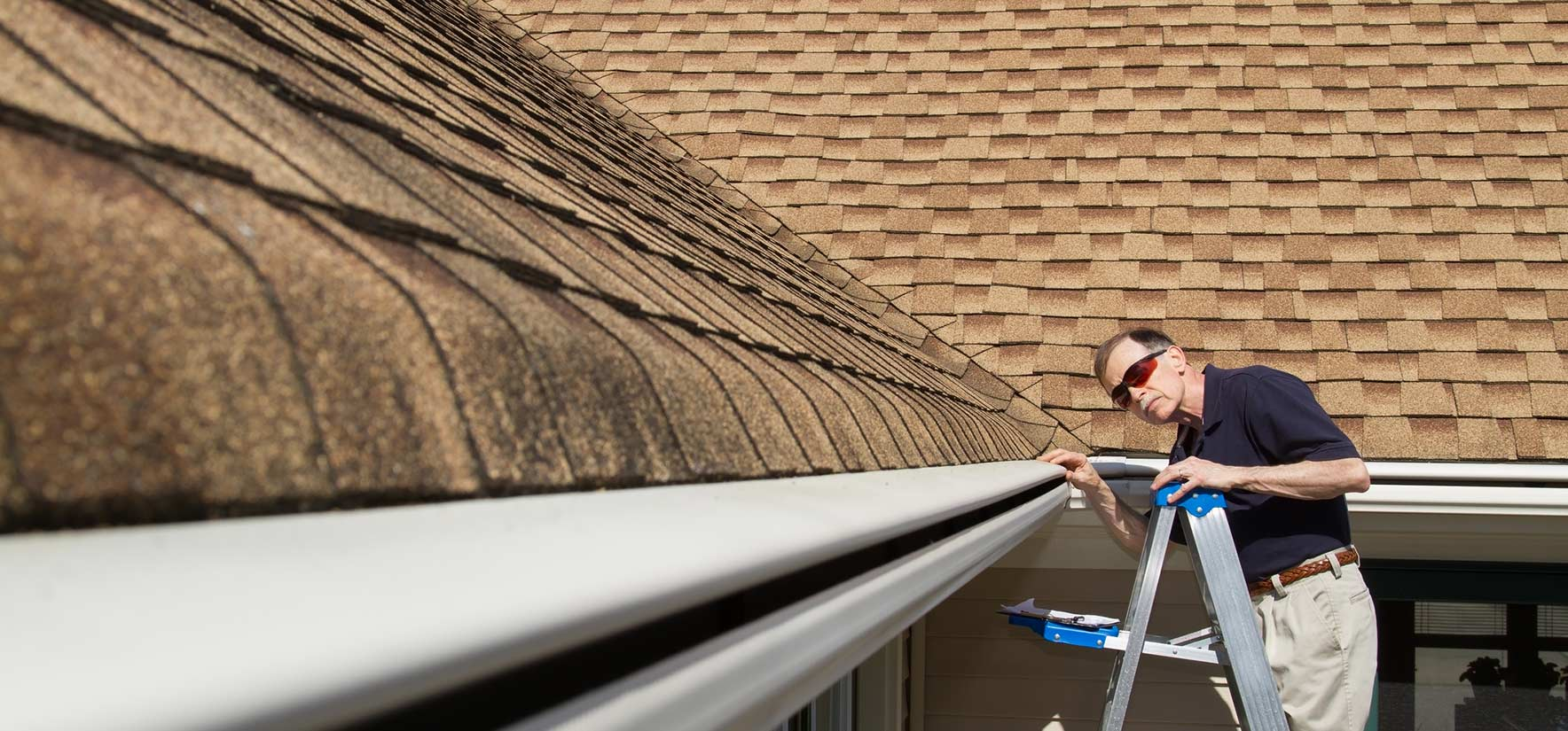 man inspecting a roof on a ladder