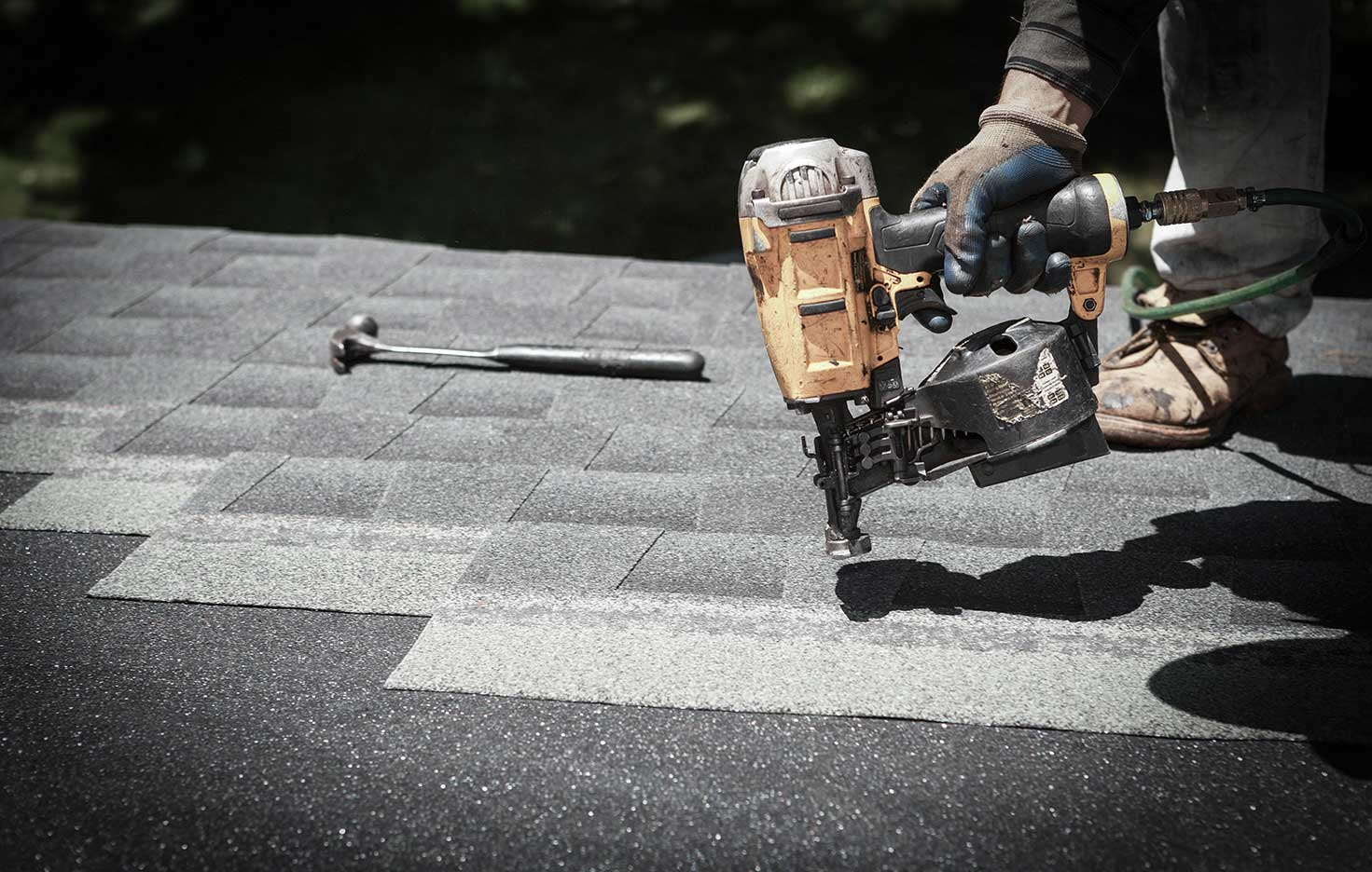 man working on a roof with hand tools